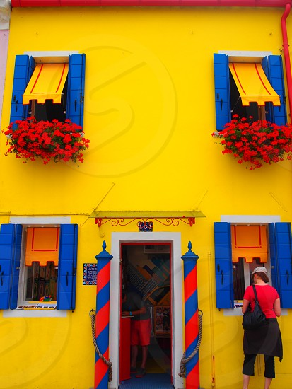 woman wearing red shirt standing at the window of blue and yellow 2 storey house during day time photo