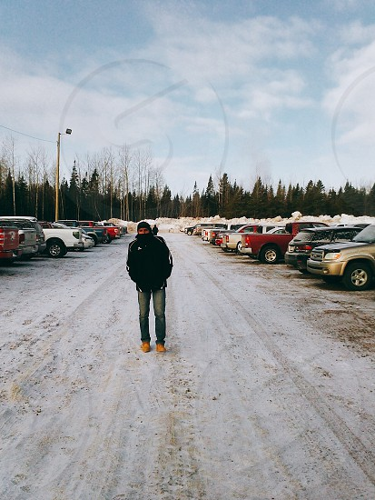 man in black jacket and blue jeans standing on snow covered parking lot under blue sky and white clouds during daytime photo