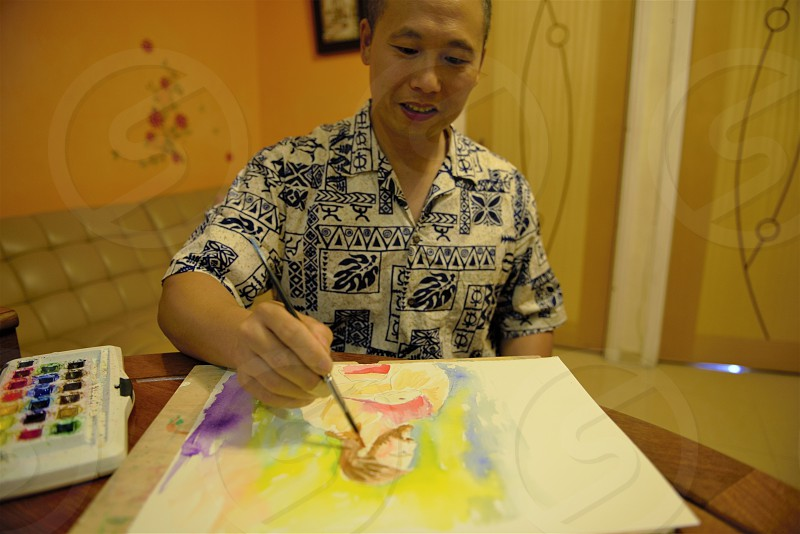 Man painting a watercolor image while in his home in Hong Kong. photo