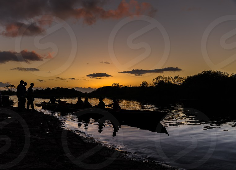 Sunset lake boat rowing people silhouette reflection pier  photo