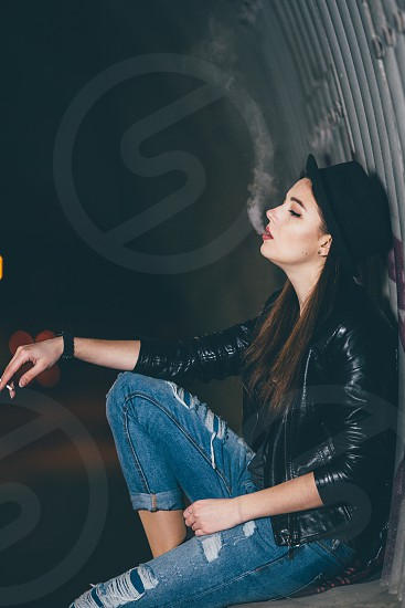 woman in black patent leather jacket sitting and leaning on wall and smoking photo