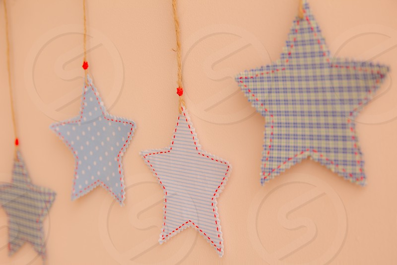 Star shaped cloth patches hanging on the wall. photo