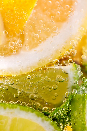 Ripe sliced pieces of lemon and lime in a glass with water and bubbles. Macro photo of summer beverage photo