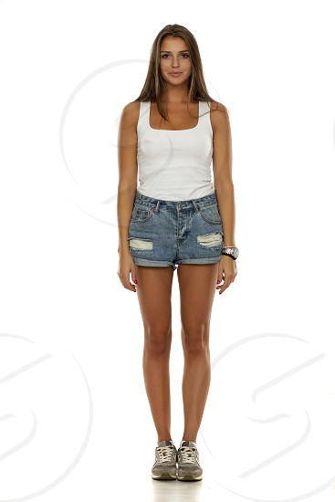 Young beautiful woman in shirt short jeans and sneakers standing on white photo