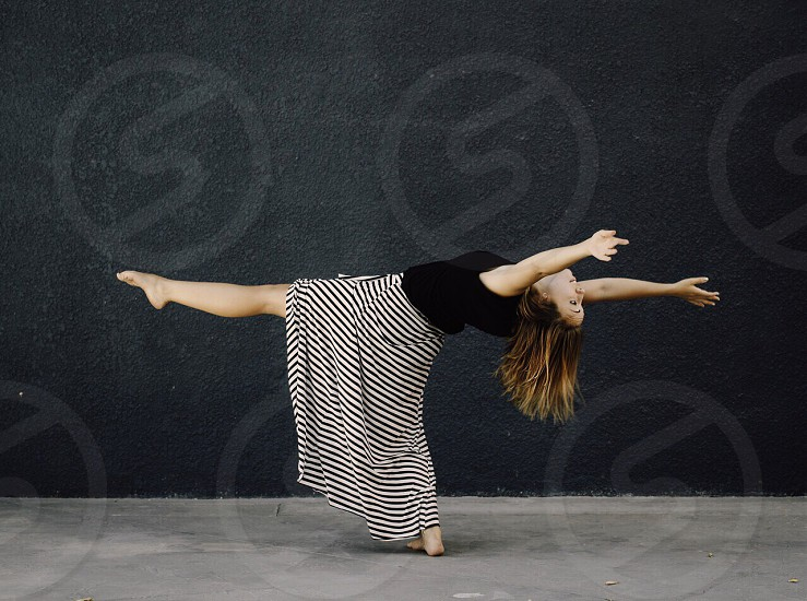 woman in black and white striped dress dancing photo