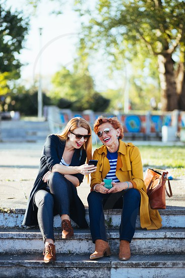 Mother and daughter in the park sharing content on their smartphones photo