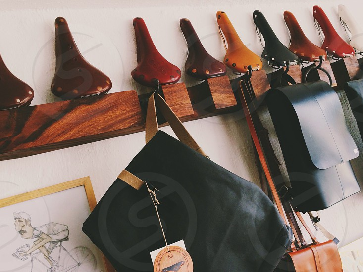 assorted sachels hanging from wooden hooks photo