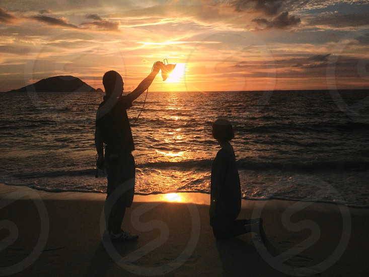 woman kneeling and man holding lamp by the sun on beach forces photography photo