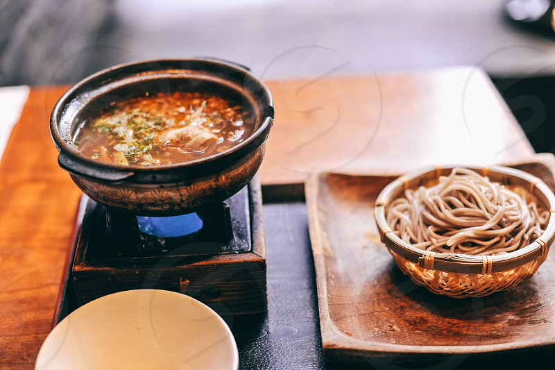 soup in bowl over burner beside pasta in brown wooden tray photo