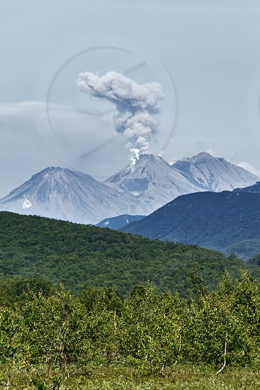 Beautiful summer mountain landscape of Kamchatka Peninsula: eruption active Zhupanovsky Volcano - volcano plume ash gas and steam from crater. Eurasia Russian Far East Kamchatka Region. photo