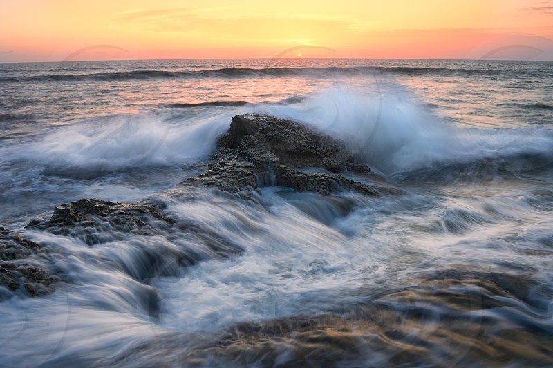 Long exposure wave crashing over the rocks under a magnificent sunset. photo
