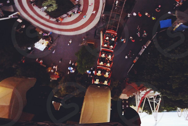 people riding on roller coaster rides in low angle photography photo