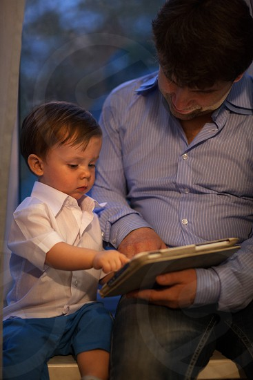 Adult man and little boy wearing white shirt play with electronic tablet sitting on the window sill photo