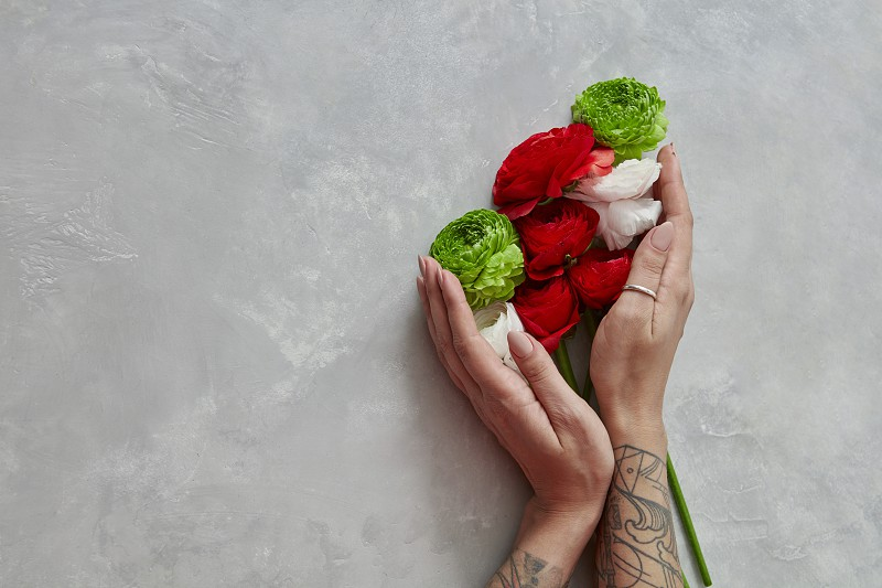 a colorful bouquet of different flowers is holding a girl on a gray concrete background. Valentine's Day or Mother's Day photo