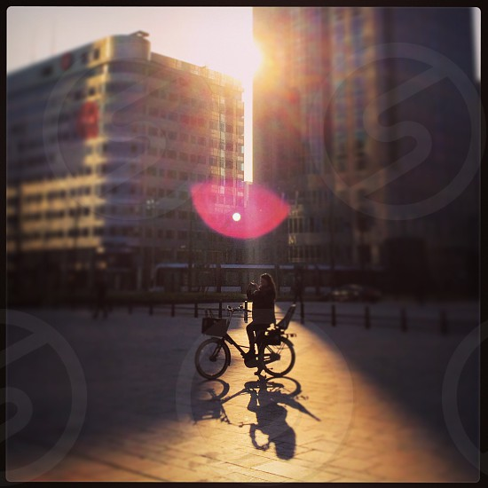 Woman on a bike taking a photograph of the central station in Rotterdam with nice backlight and lensflare photo
