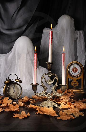 Candles among the fallen leaves with a clock and ghosts photo