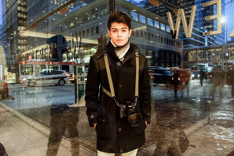 boy in black button-up coat with camera in front of glass window photo