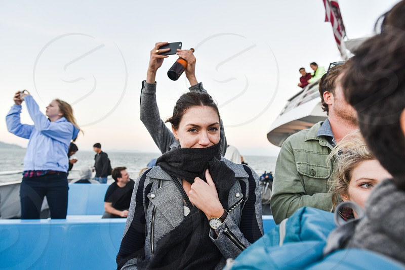 woman covering mouth with black scarf surrounded by people taking photos photo