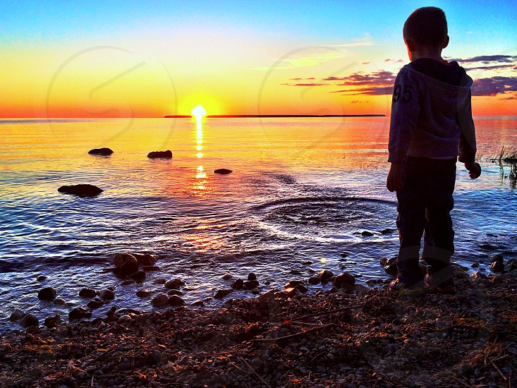 Silhouette of boy throwing rocks in Lake Michigan at sunset beach in door county. photo