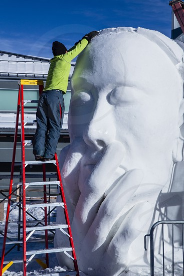 Man sculpting snow into image of a large face at Breckenridge Colorado ice festival. photo