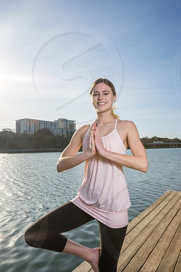 Beautiful happy woman outdoors near the water. Can be kept with the other bank of the river or photoshopped for an ocean horizon.  photo