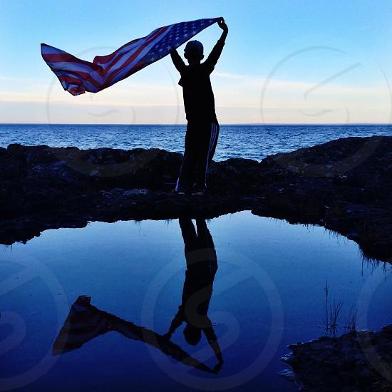 boy holding usa flag on the seashore photo