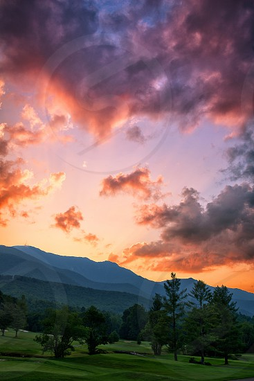Sunset over golf course and mountains. photo