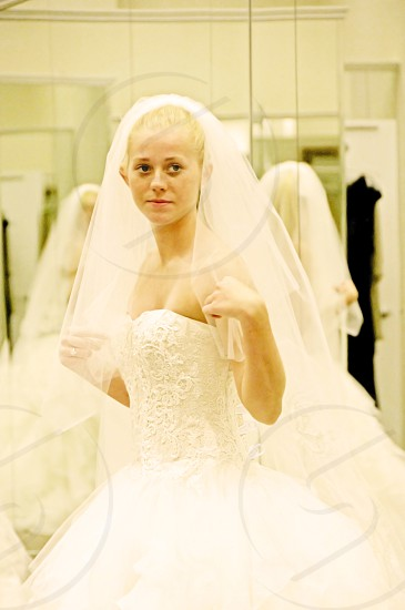 young lady trying on wedding dresses photo