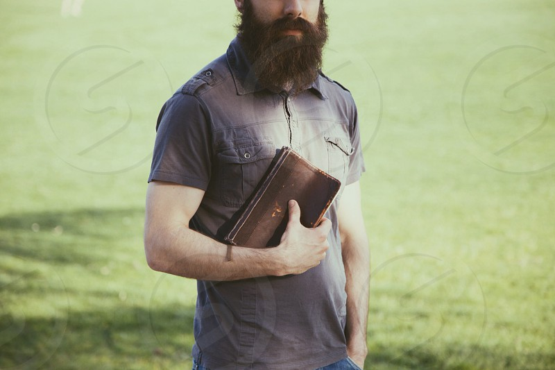 man in black polo shirt holding brown book photo
