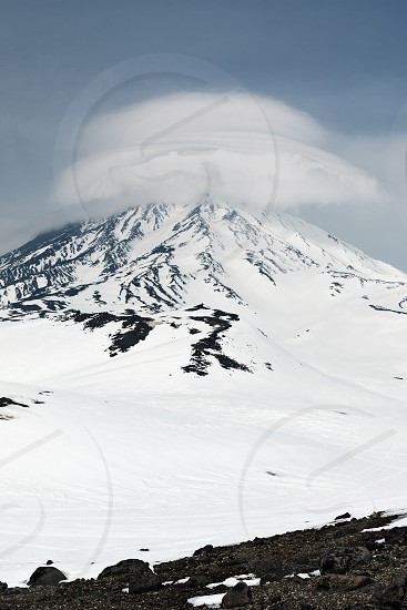 Wintry mountain landscape of Kamchatka: beautiful view of Koryaksky Volcano (Koryakskaya Sopka) and clouds enveloping the top of the active volcano. Kamchatka Far East Russia. photo
