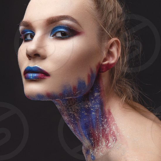 Studio Portrait of a young model girl with stylish makeup in a dark blue tones photo