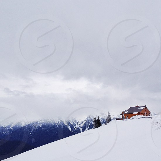 brown painted house on snow mountain photo