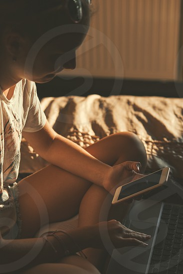 Young woman using portable computer and mobile phone sitting on a bed learning online at home. Candid people real moments authentic situations photo