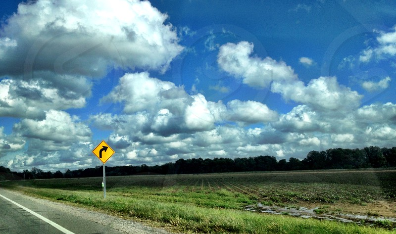 yellow right curved road sign on green short grass under blue sky and cumulus clouds at daytime photo
