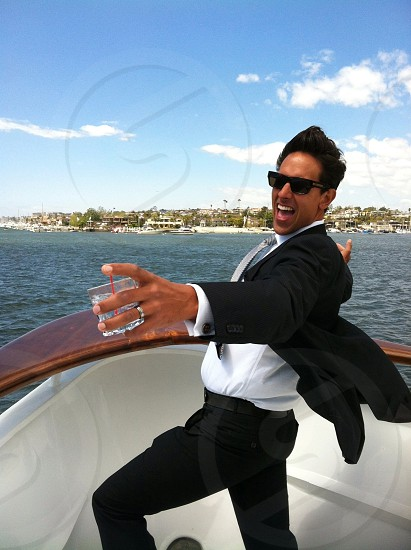 man wearing black formal suit on white yacht photo