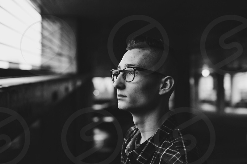 grayscale photo of man wearing eyeglasses and shirt looking on his left side photo
