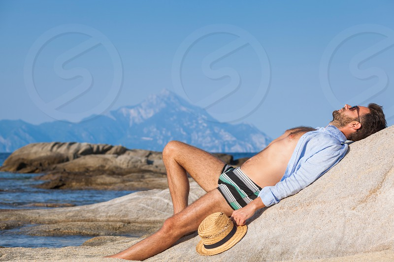 Young man relaxing on the beach sunbathing on a rock near the sea photo