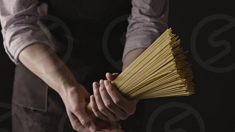 The bunch of raw uncooked italian spaghetti in a woman's hands on a dark background. Slow motion Full HD video 240fps 1080p. photo