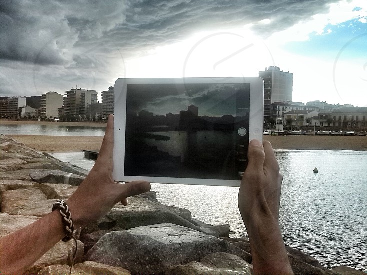 person holding white ipad taking photo photo
