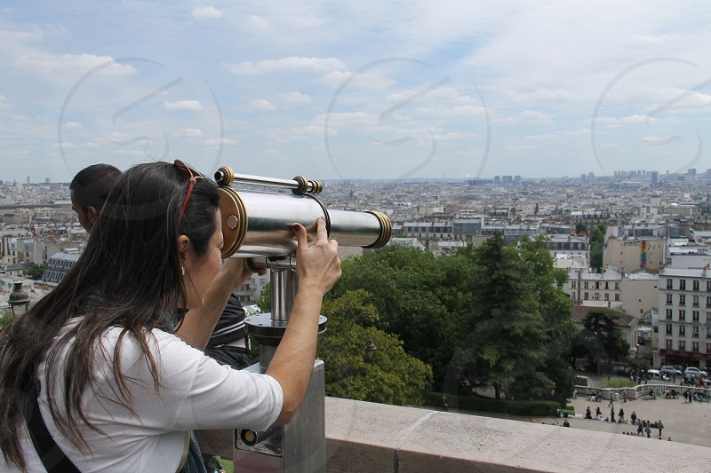 woman using telescope looking down photo
