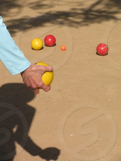 A female player is ready to toss her yellow bocce ball toward the pallino or jack in the traditional Italian bowling game.  photo