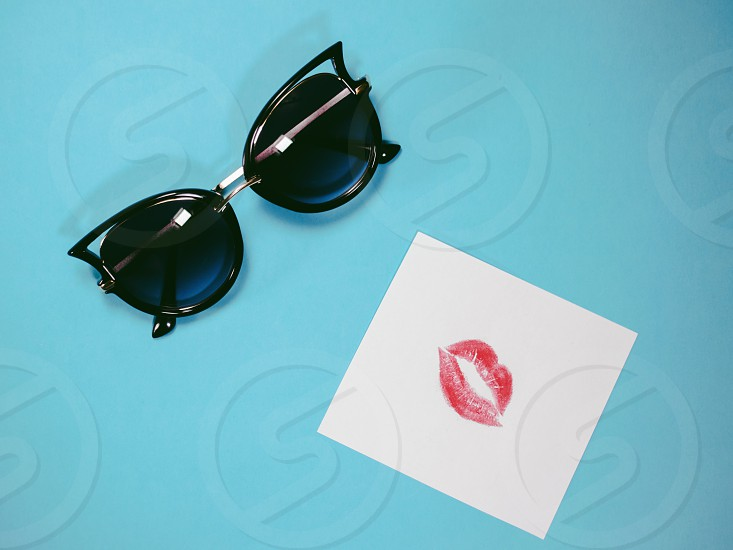 Emotional faces: black sunglasses and colourful print of lipstick on paper photo