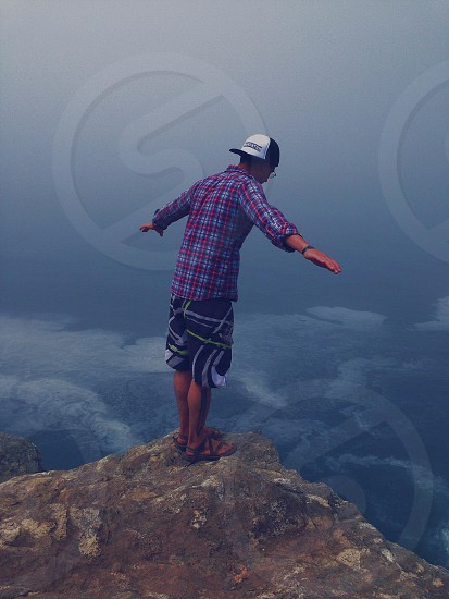 man standing on edge of cliff photo