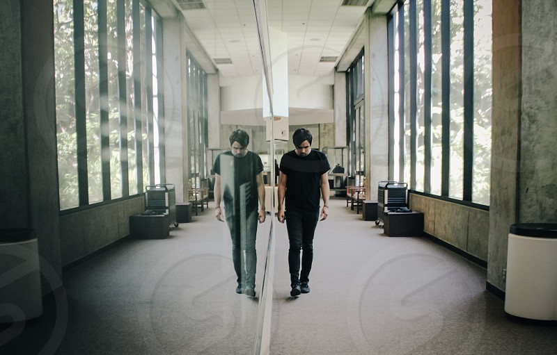 man walking beside a mirrored wall photo