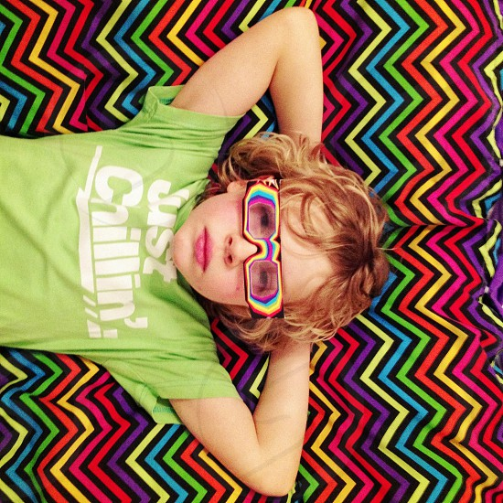 boy lying on assorted color chevron bed blanket photo