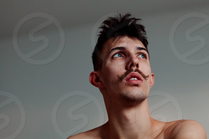 Young shirtless man with mustache thinking photo