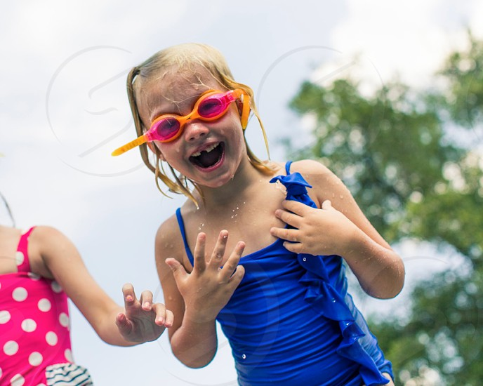 girl in blue swimsuit smiling wearing pink and orange goggles photo