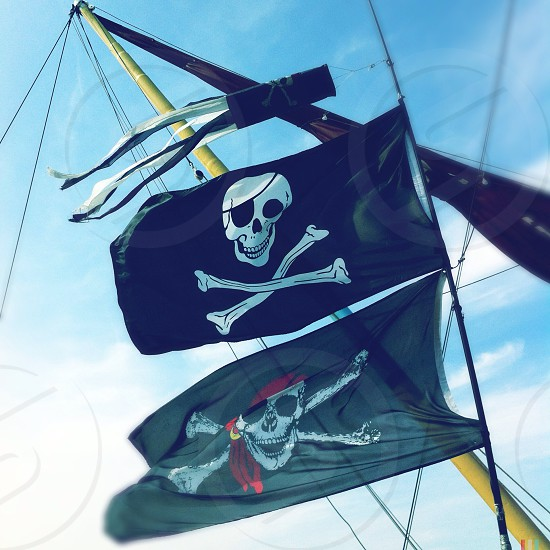 Pirate skull and crossbones flags fly in the wind aboard a ship in Whitstable England.  photo