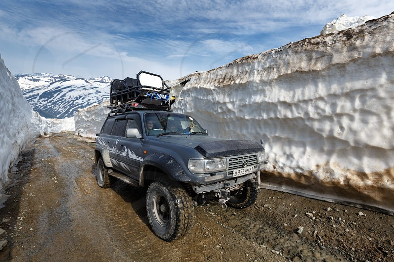 KAMCHATKA PENINSULA RUSSIA - JUNE 18 2017: Japanese extreme off-road expedition car Toyota Land Cruiser driving on mountain road in snow tunnel surrounded by high snowdrifts on Vilyuchinsky Pass. photo