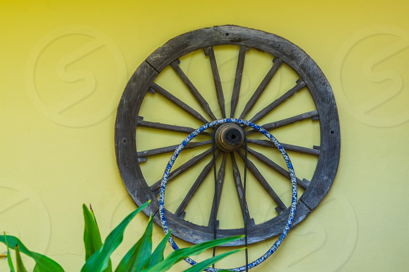 An old wooden cartwheel on a wall. photo